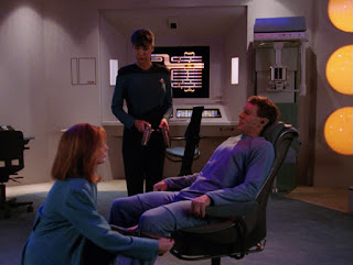 Dr. Crusher kneels before a patient in a chair, dressed in blue, while a nurse reports on the results of an examination in a medical lab.