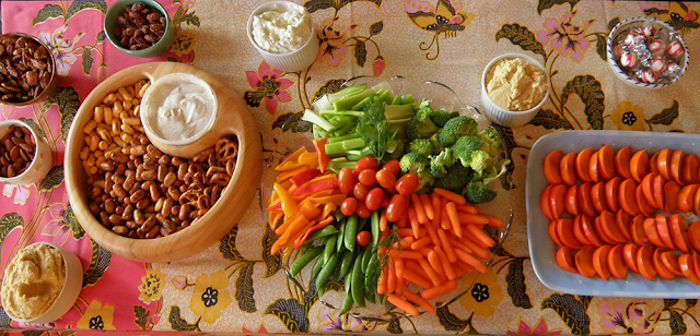 Table with Assorted Veggies, Dips, Persimmons, Nuts, and Pretzels