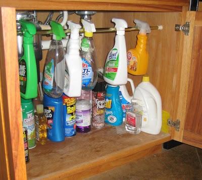Organizar armário de limpeza com uma barra para pendurar os produtos