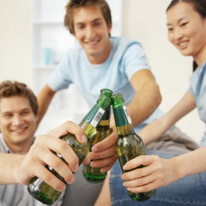 Three friends toasting with beers in a bottle.