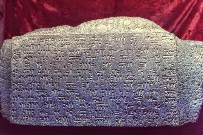 Frame of cuneiform recording from Urartu fortress laying on red fabric