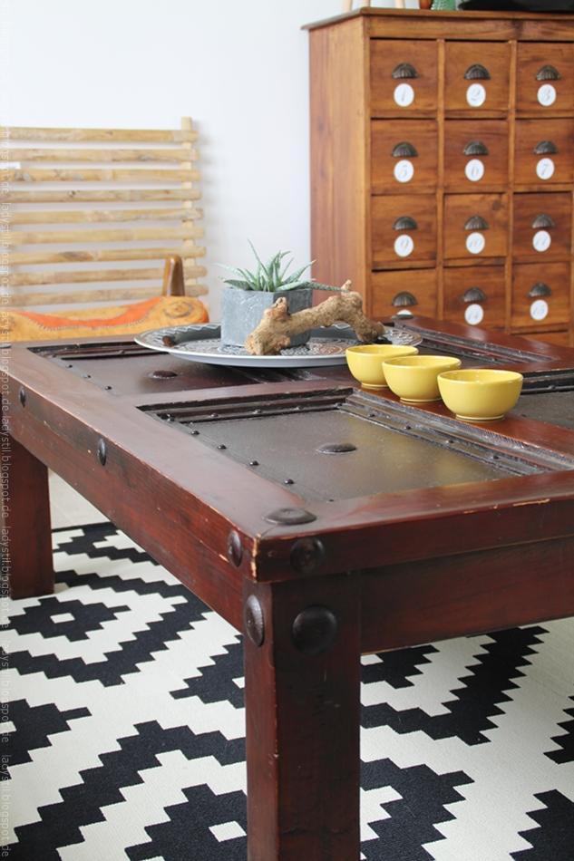 dunkler Tisch mit Tablett und Kaktee vor einem Wandboard