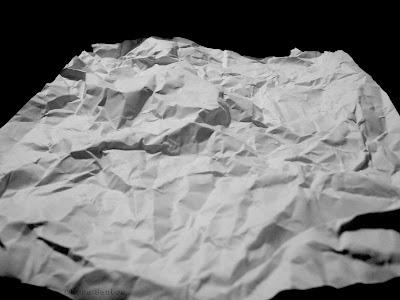 Fotografia P e B. É vista uma folha branca de papel amassado sobre fundo preto. Na imagem, de baixo para cima, a largura da folha se reduz e desaparece no fundo. A luz vem de cima e se espalha em toda a superfície, há sombras entre os relêvos, gerando as irregularidades de altos e baixos na superfície, brancos onde há luz, e cinzas onde há sombra.