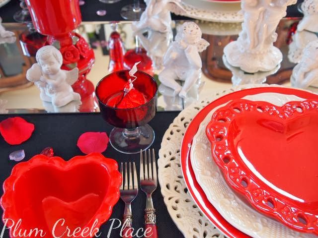 Valentine's day tablescape, red heart plates, mirror centerpiece, cherubs, red wine glasses, pierced white charger plate, pierced red heart salad bowl