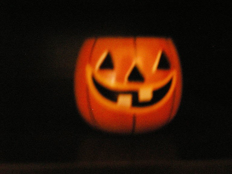 A jack-o'-lantern made of tin and hand-painted.