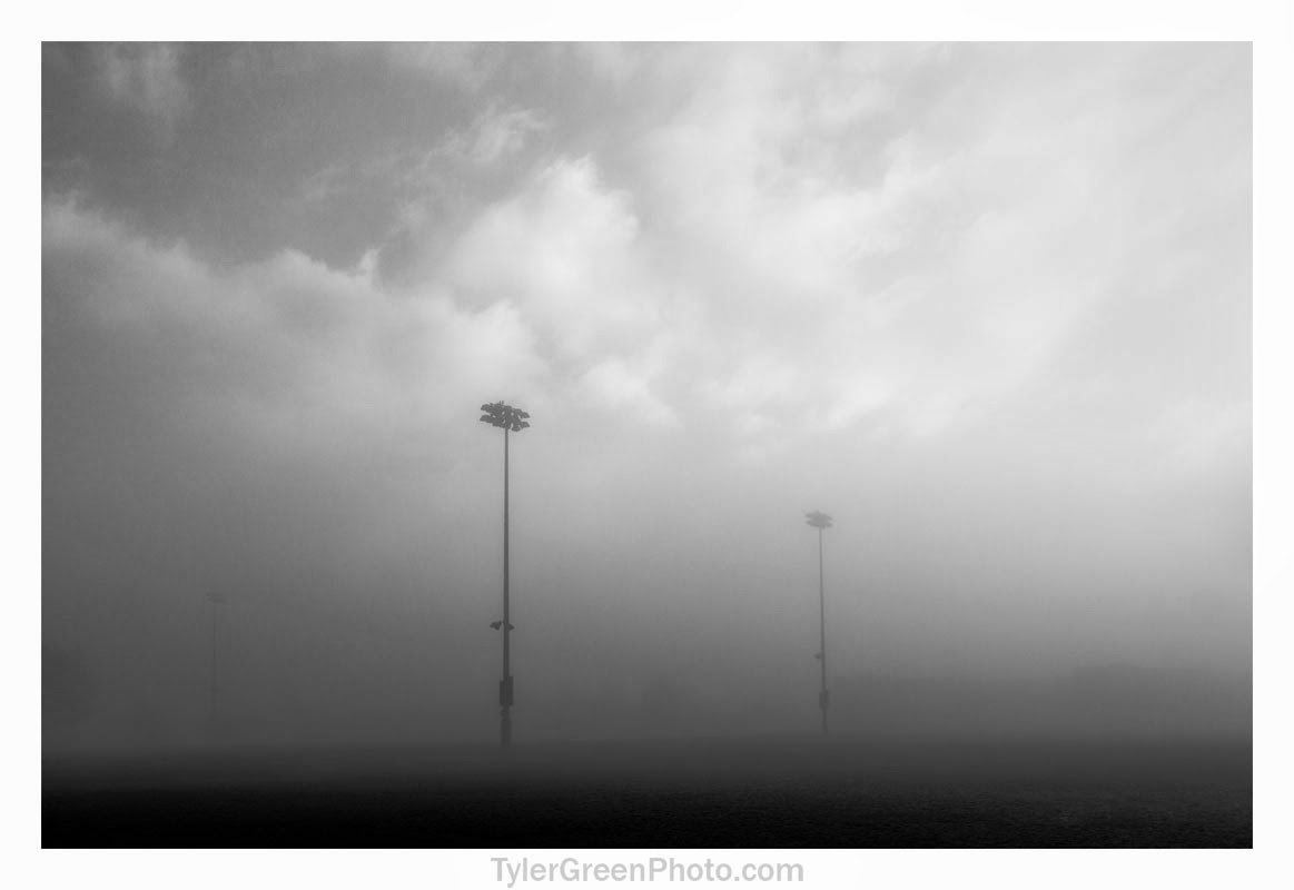 Two light poles stand alone in a sea of fog