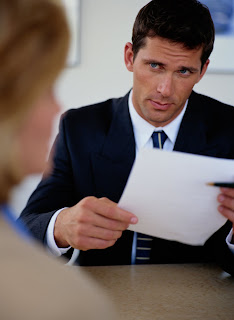 Picture of a man interviewing someone with a paper in his hand.