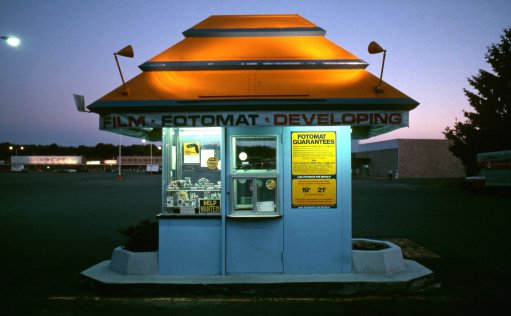 vintage 1970s fotomat booth at night