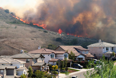 Image of wildfire burning on a hil with a residential neighboorhood at the foot of the hill.