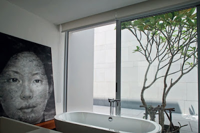 A cool en suite bathroom looks into a courtyard
