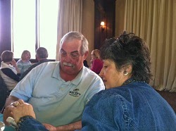 Grey haired man with mustache in a lite blue shirt and woman with dark hair in blue jacket sitting at a table looking at the same photo.