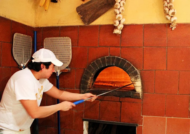 pizza being placed in wood fired brick oven