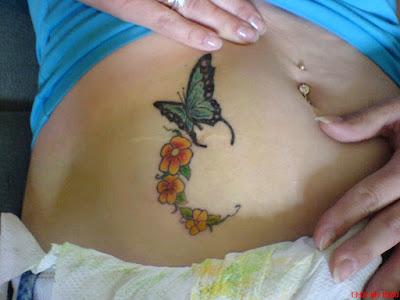 Tatuaje mariposa y flores en el abdomen