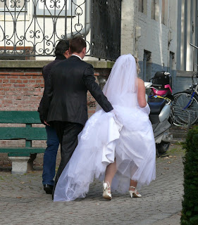 funniest wedding picture: the bridegroom holding her wedding dress