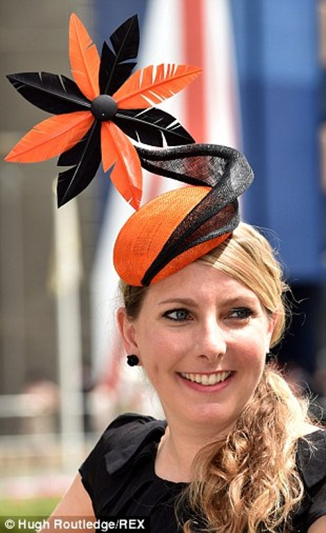 a lady in an orange and black sunflower hat on day four of Royal Ascot 2014