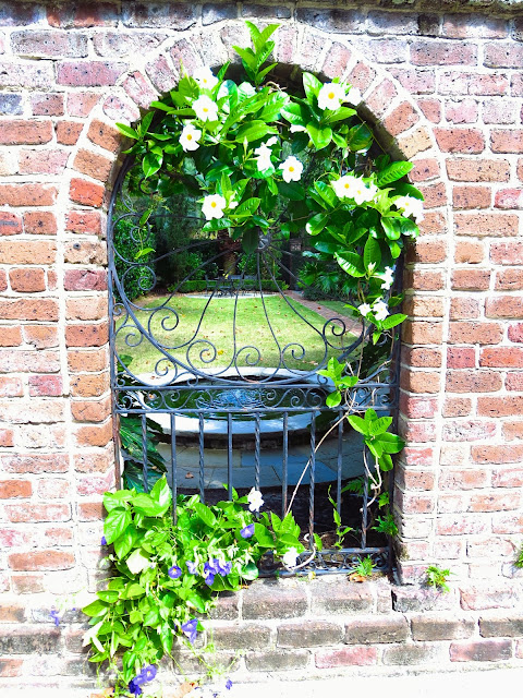 Brick arch and wrought iron garden gate window in Charleston, South Carolina