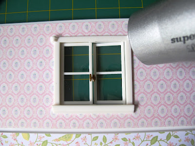 Hairdryer pointed at a window on the wall of a Lundby Smaland dolls' house.