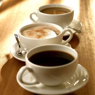 Tres tazas de café, con sus platillos y cucharitas