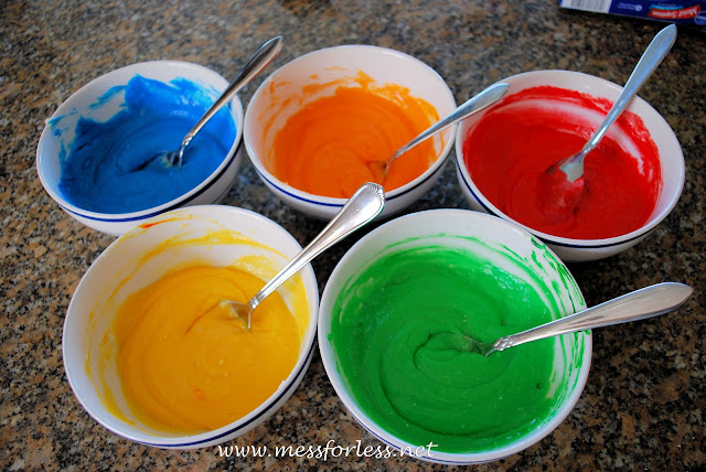 adding food coloring to cake batter for rainbow cupcakes