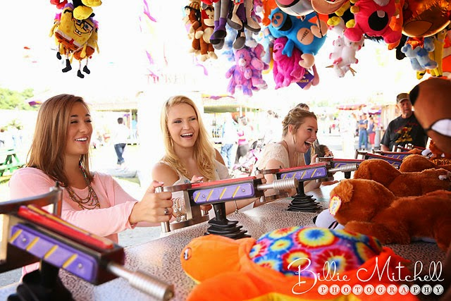 senior girls laughing while playing carnival games at the county fair