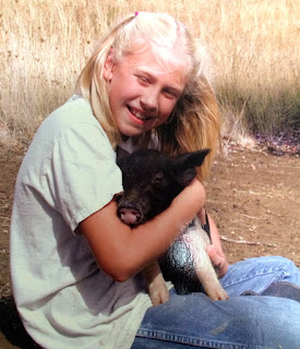 A girl holds her baby piglet