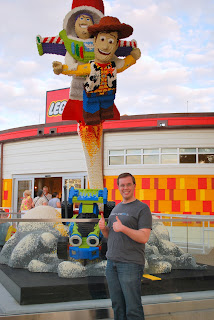 B standing in front of a Lego sculpture of Buzz and Woody (from Toy Story) blasting off on a rocket from RC.