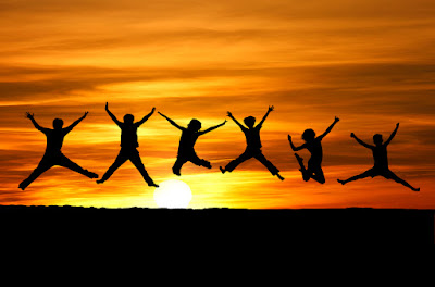 6 people are leaping into the air with the sunset and horizon in the background