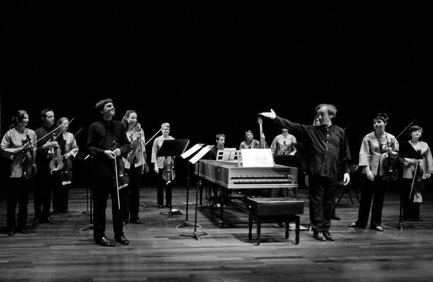Elementos da orquestra, de pé.  O maestro de braço estendido, dirigindo os aplausos para o músico - primeiro violino.