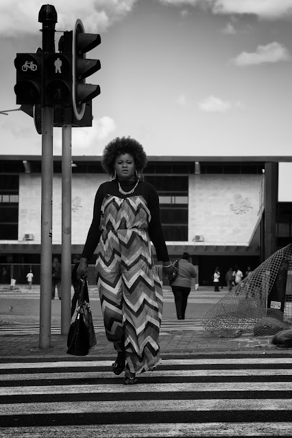 A woman in a striped outfit crosses the road at a zebra corssing