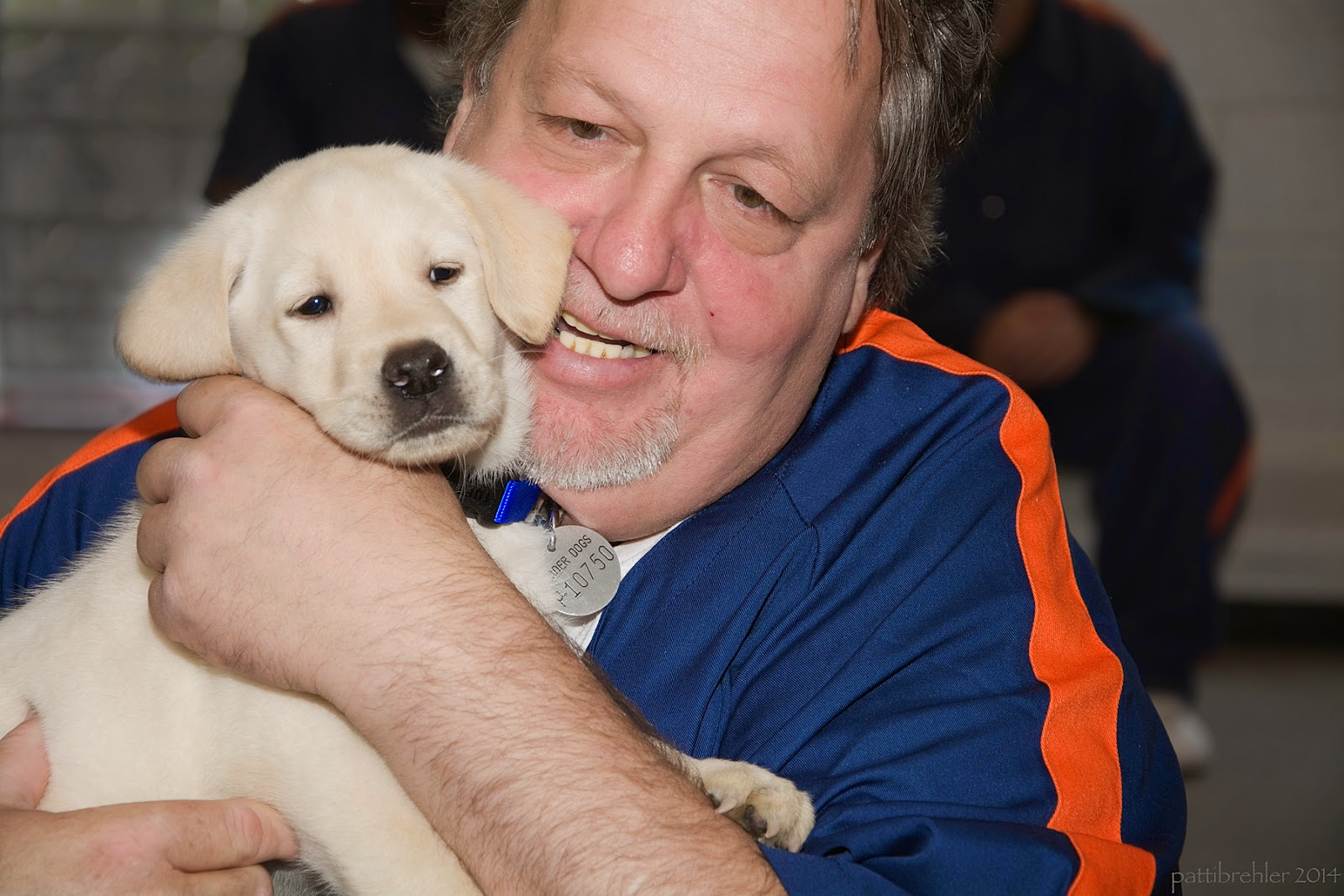 A close up shot of a man holding a small yellow lab puppy in his arms. The puppy is facing the camera with his head pressed against the man's right cheek. The man is wearing the blue and orange prison shirt and his left hand is embracing the puppy's neck and shoulder.