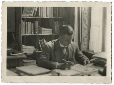 Altes Schwarz-weiß-Bild mit Mann am Schreibtisch vor einem Regal