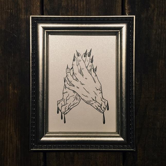 A framed print of Soren Häxan's ink illustration 'Dead Hands' against a dark wood background.