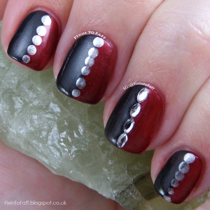Half red, half black nail art with silver chrome dotting.