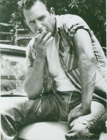 Kevin Costner smoking a cigarette (or weed)