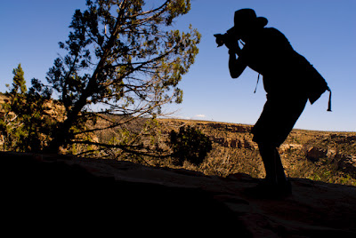 Jeremy Wade Shockley silhouetted against a morning blue sky at Mesa Verde National Park.