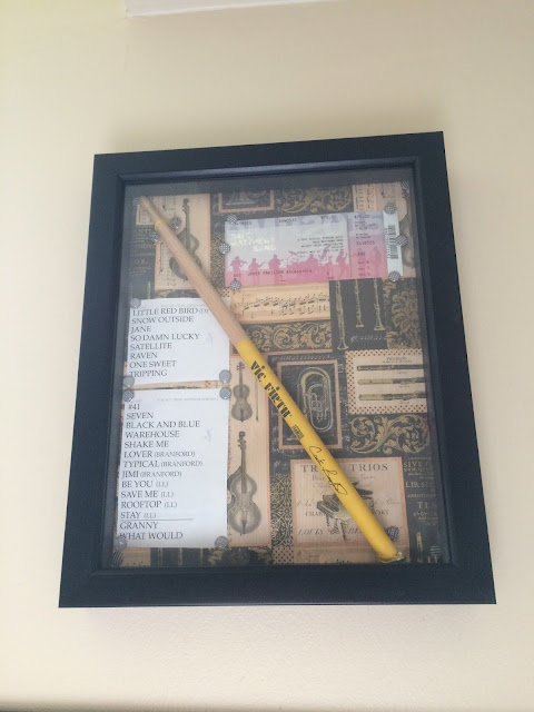 Photograph: A 3D picture frame with a background of printed instruments. Displayed are a set list, fan club ticket, and drumstick.