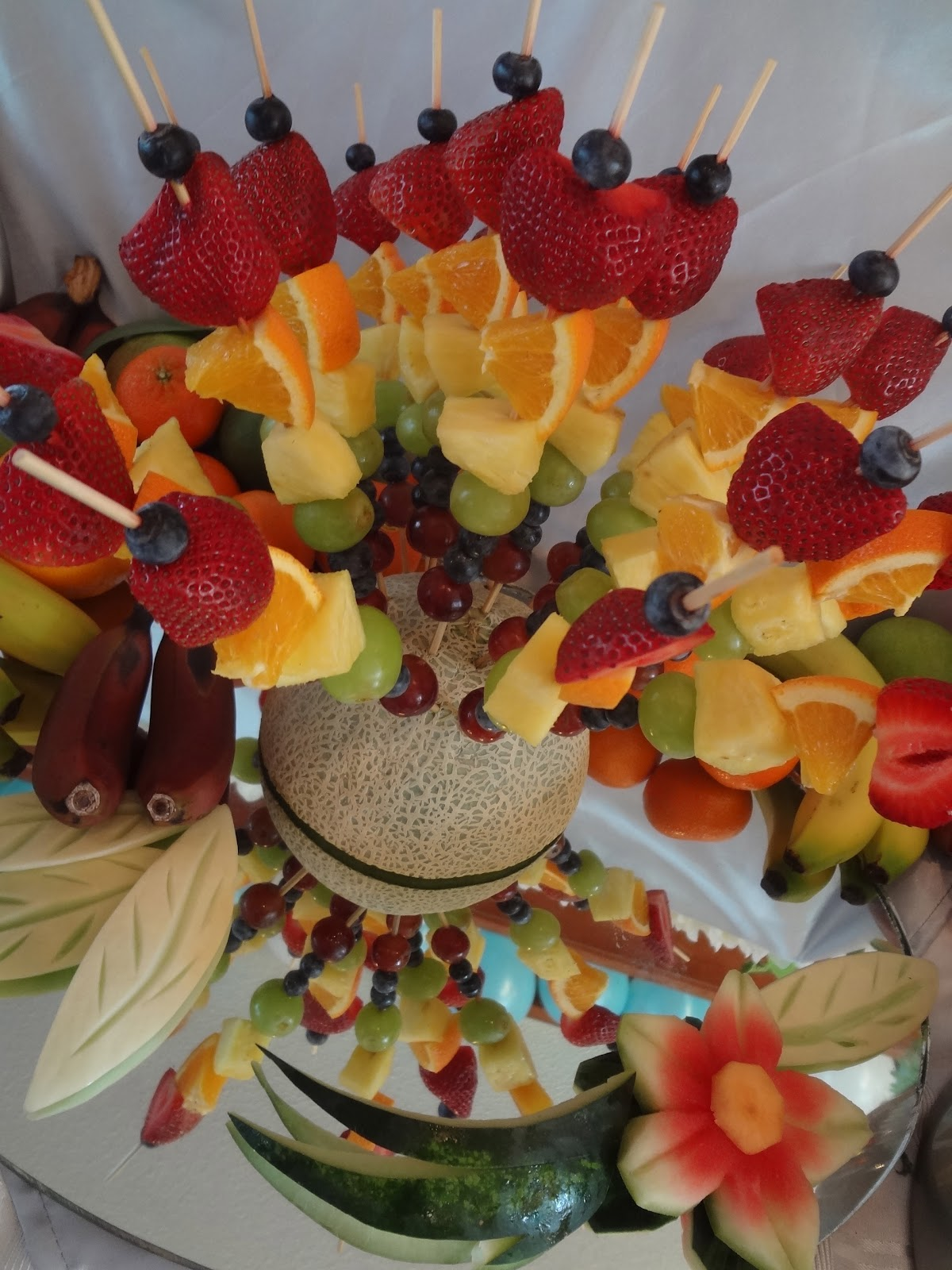 Fruit kabobs! We stuck them into a half melon, and then set the whole ...