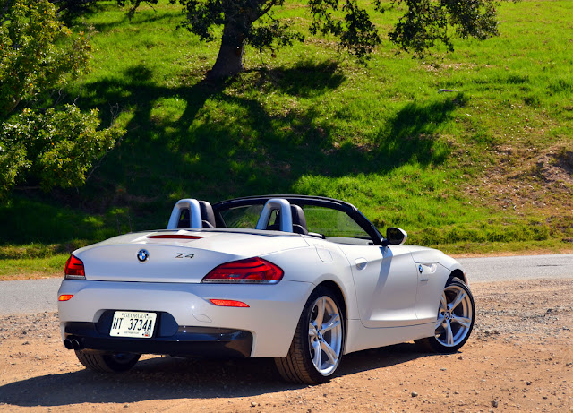 Rear 3/4 view of white 2012 BMW Z4 roadster parked with top down in rural setting