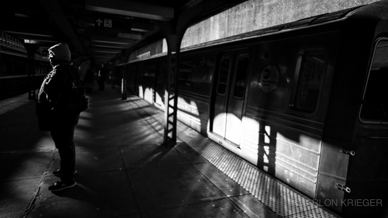 A women stands on the Q Train platform in brooklyn