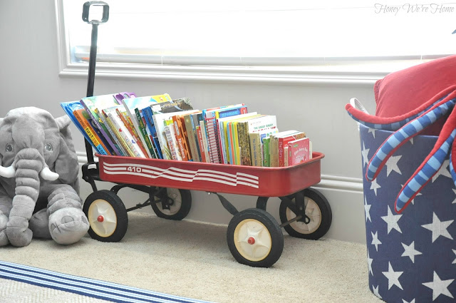 An old red wagon doubles as book storage in a kid's room