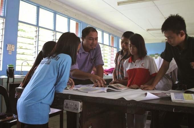 Cikgu Hailmi membimbing pelajar semasa sesi pembentangan
