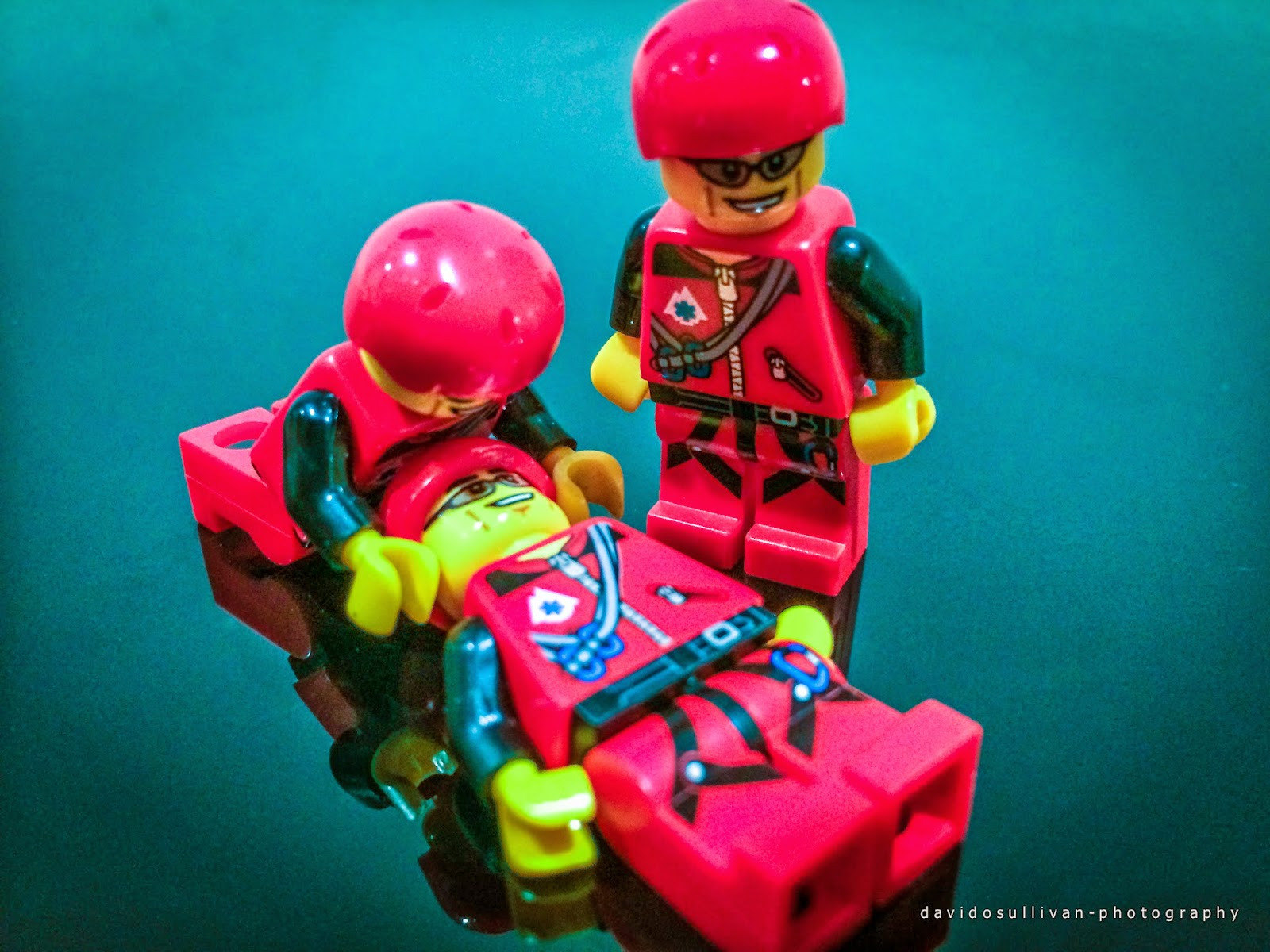 Two Lego Mountain Rescue figures practising Casualty Care on a third figure