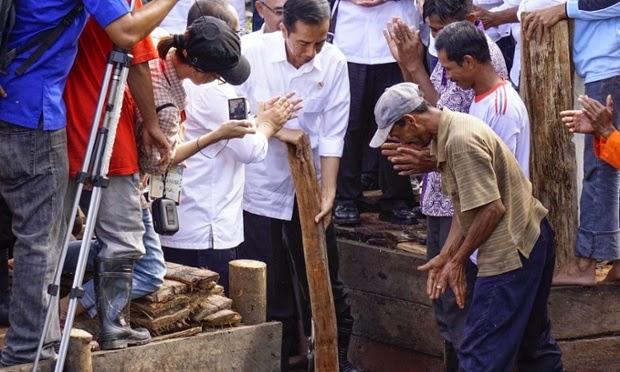 Indonesian President, Joko Widodo joins members of the Sungai Tohor community in damming a canal draining peatlands on Tebing Tinggi island on Thursday. (Credit: Ardiles Rante/Greenpeace) Click to Enlarge.