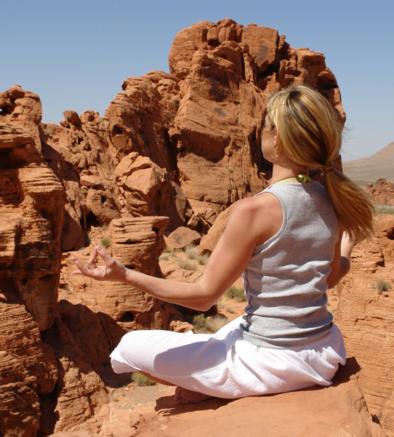 young blonde woman practices desert yoga