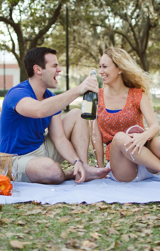 couple popping champagne cork during their engagement session