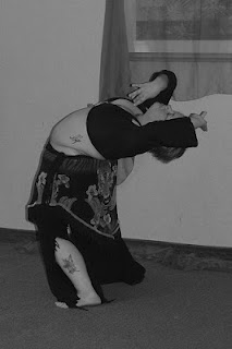 Author in 2009 bellydancing. Photo is black & white, with short hair, black long sleeved crop top, tiger print hip shawl, and black flared pants with tattoo showing on pale skin, performing a standing layback.