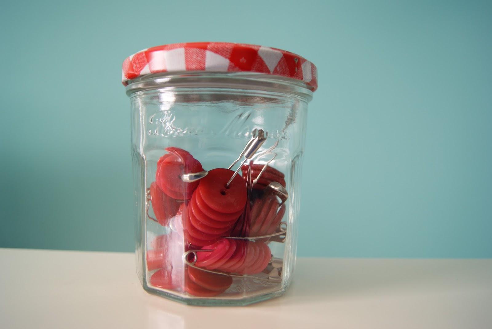button storage on large safety pins, all same color buttons in one jar by nest full of eggs