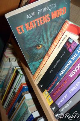 bokryggar i bokhylla, med en bok utdragen. Et kattens mord. foto: Reb Dutius