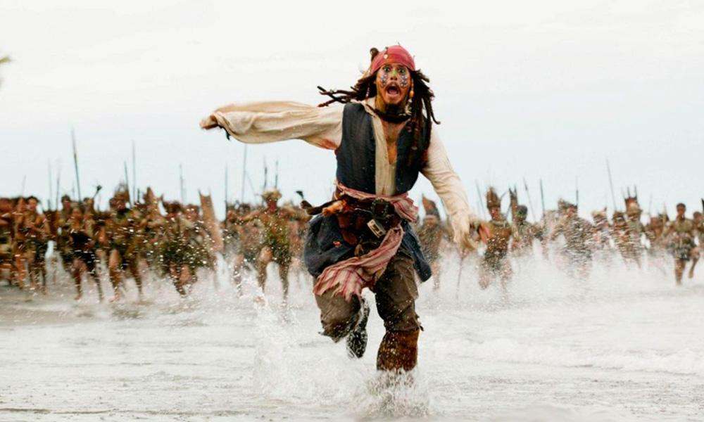 Cena do filmes Piratas do Caribe - O Baú da Morte (2006) onde o Capitão Jack Sparrow aparece fugindo de um bando de selvagens