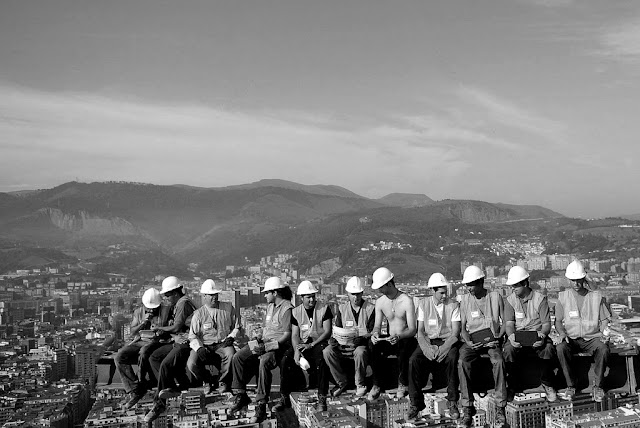 Black and white photo of workers on the skyscraper with the city skyline in the background
